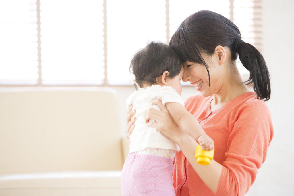 育児中に赤ちゃんに微笑むかけるお母さん